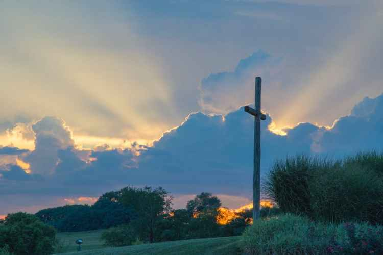 cross on hill at sunset